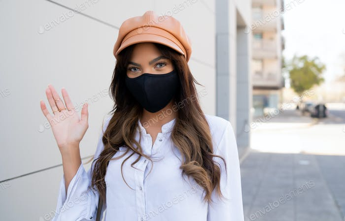 Young woman wearing protective mask outdoors.