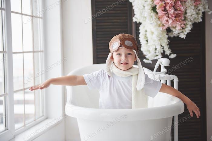 Happy kid in pilot hat playing in bathroom. Childhood. Fantasy, imagination.