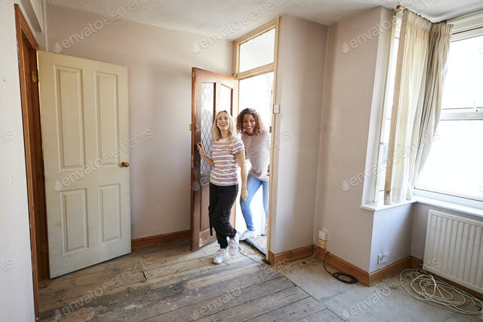 Excited Female Couple Opening Front Door Of New Home