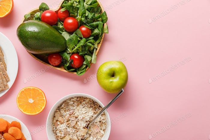 top view of fresh diet food on pink background with copy space