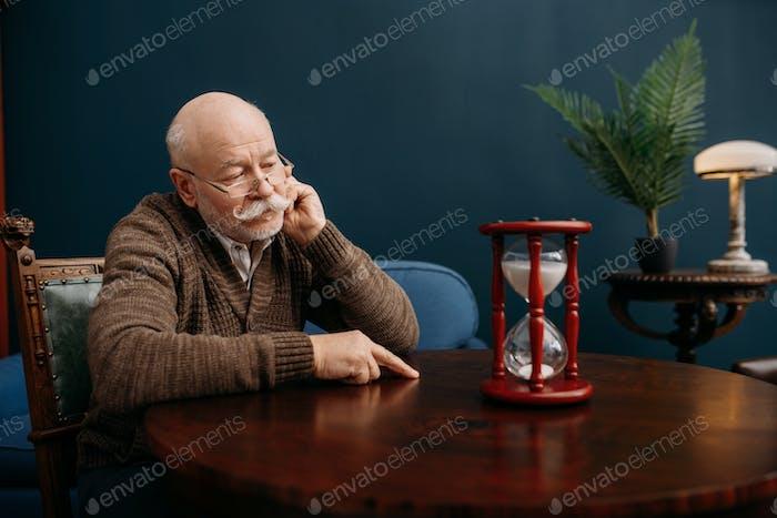 Elderly man looking on sandglass in home office