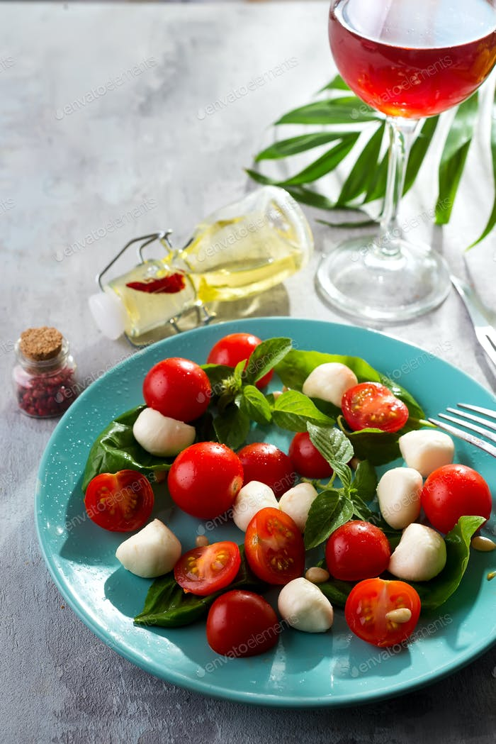 Italian Caprese salad with red tomatoes, fresh organic mozzarella and basil on stone table, Top view