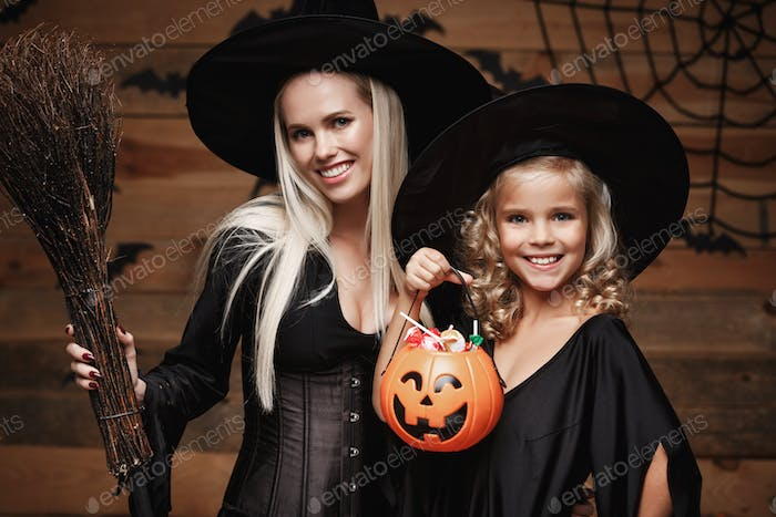 Halloween Concept - beautiful caucasian mother and her daughter in witch costumes celebrating