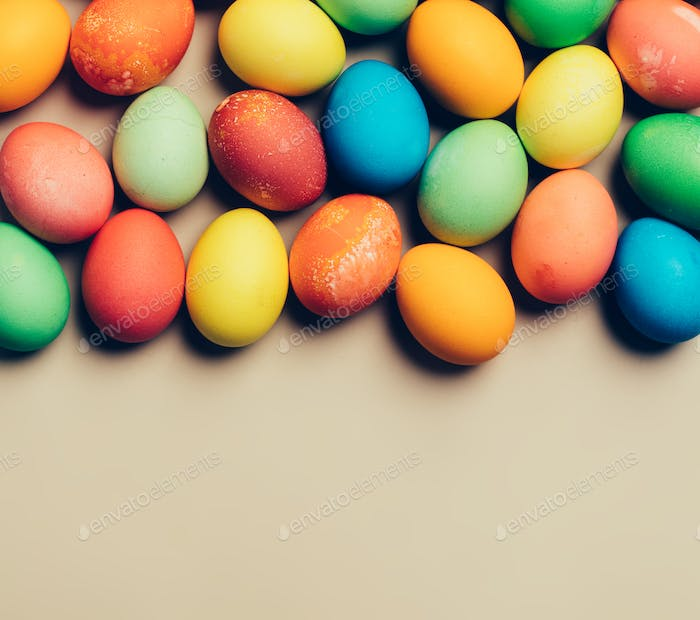 Textured colorful eggs laying on the beige background.