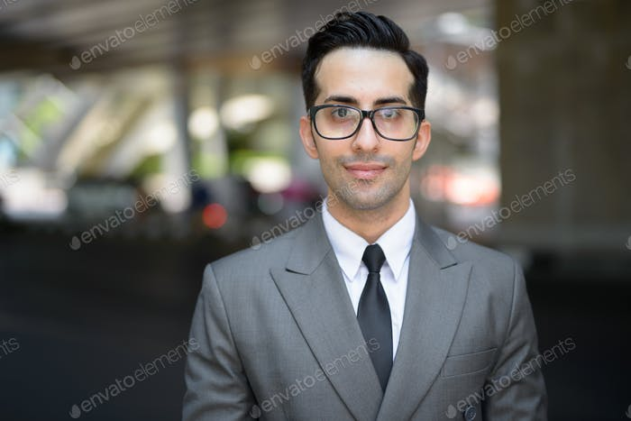 Face of young handsome Persian businessman in the city streets outdoors