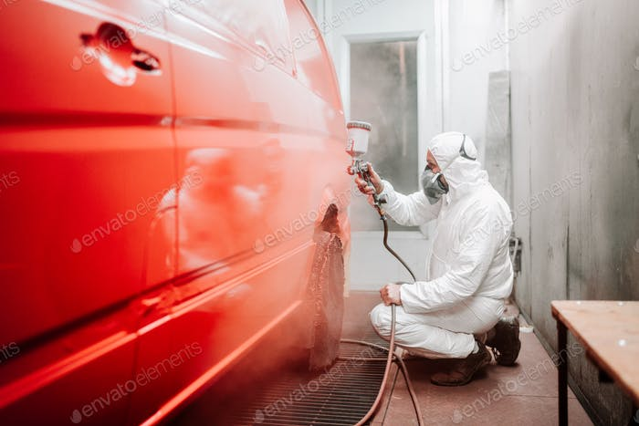 Auto mechanic working in automotive manufacturing industry and painting a red van in a special booth