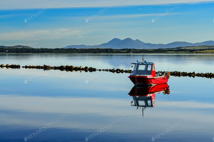 Small red boat in peaceful harbour