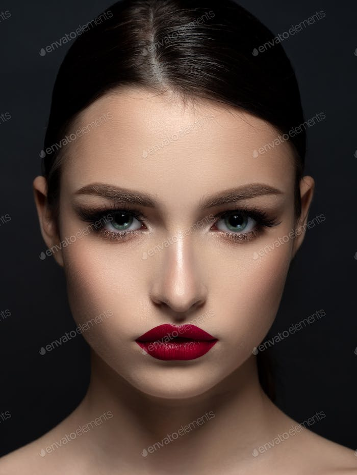 Portrait of young beautiful woman with red lips