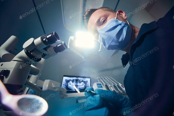 Zahnarzt untersucht Patienten mit zahnärztlichen Ausrüstungen