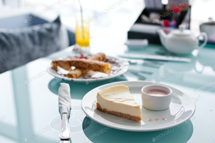Slice of cheesecake on white plate and glass table in cafe