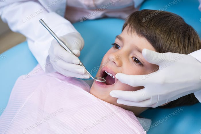 Cropped image of dentist holding equipment while examining boy