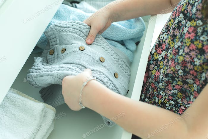 Small baby knitted clothes in hand older sister. Home, life style concept