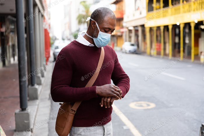 African American wearing covid19 coronavirus mask and using his smartwatch in the street