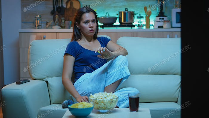 Lonely woman watching TV in evening