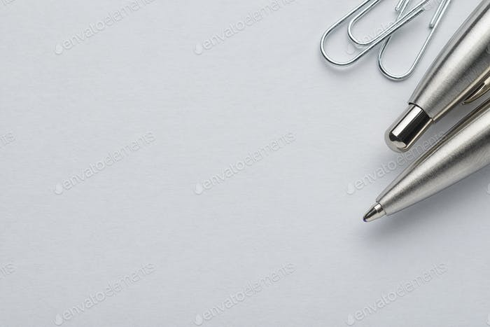 Metal ballpoint pen and paper clips on white paper