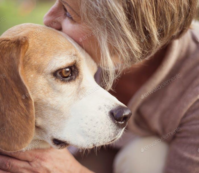 Active senior woman hugs dog
