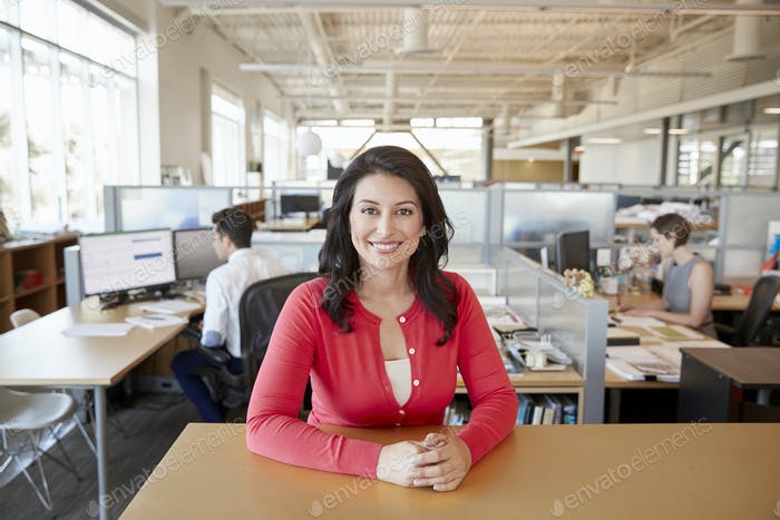 Smiling female architect at a desk in busy open plan office