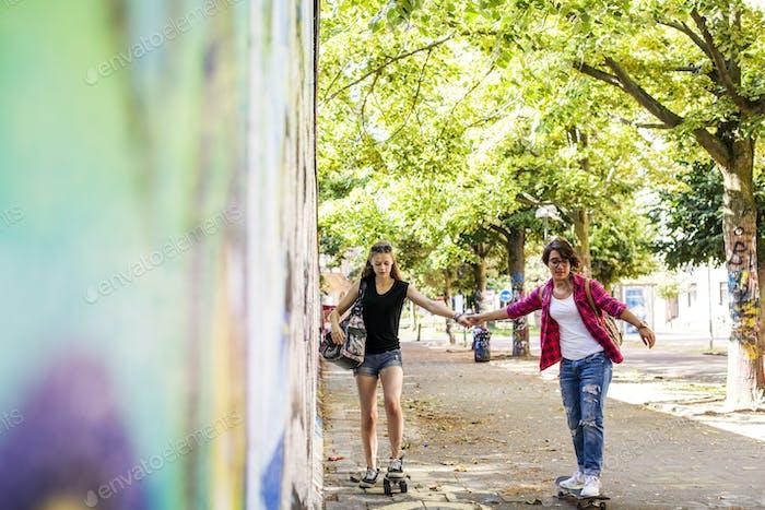 Teenage girls skateboarding at footpath by wall