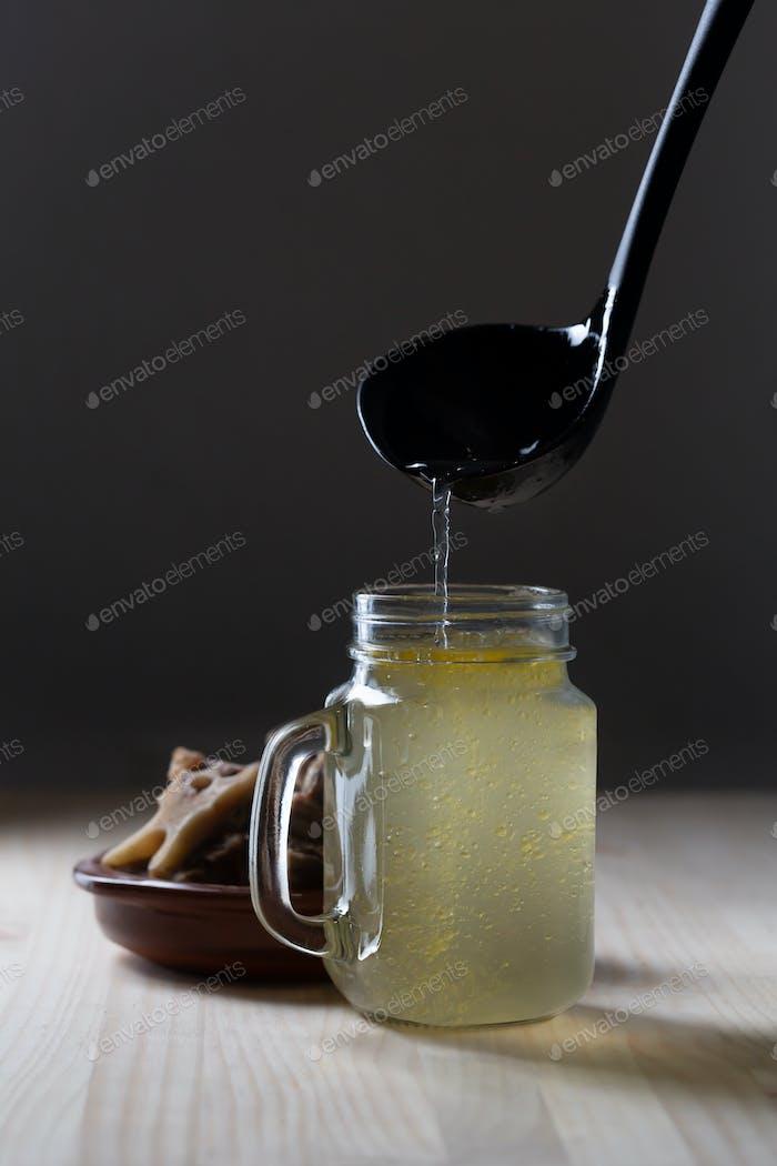 Homemade Beef Bone Broth in Glass Storage Jar on a black background
