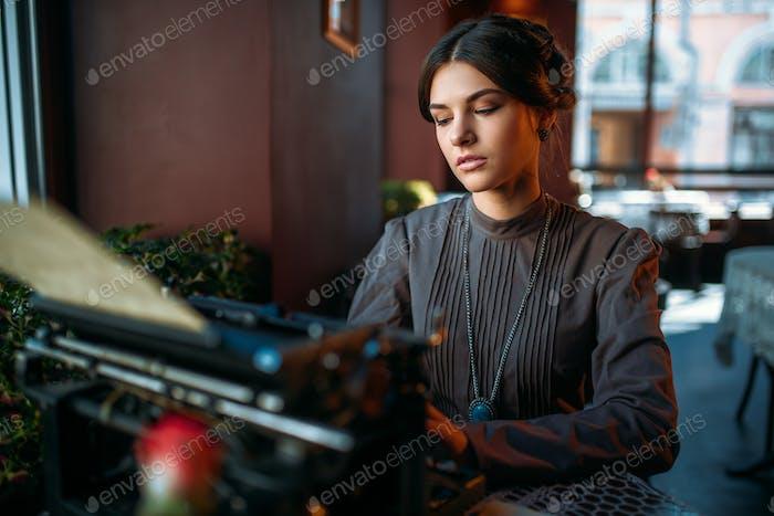 Serious lady prints on ancient typewriter