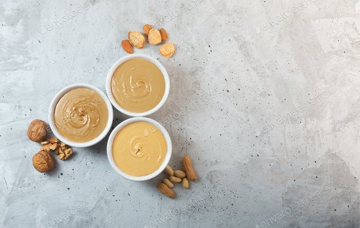 Peanut, walnut and almond butter on the gray concrete background, top view, copy space