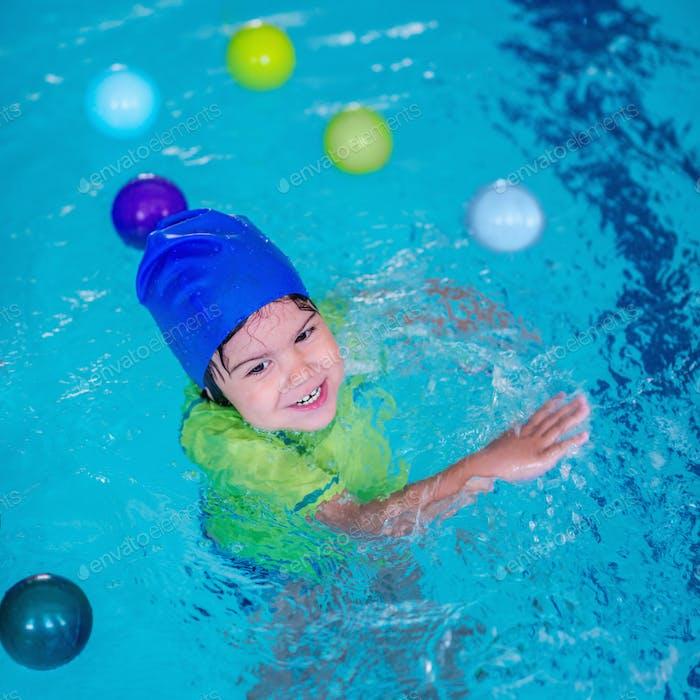 Cute little child having fun in a swimming pool