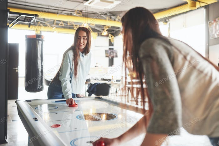 Two beautiful twin girls play air hockey in the game roomand have fun