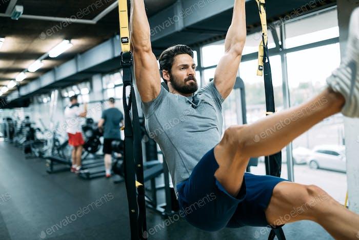 Caucasian man exercising with suspension training trx