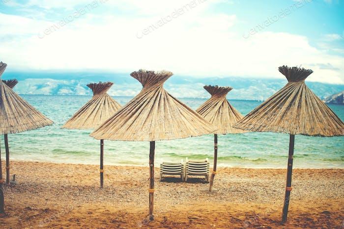 Instragram retro effect on photo, beach umrellas with straws and shade on beach, coastline landscape