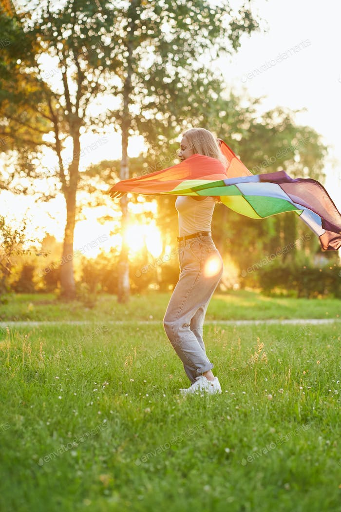 Laughing woman dancing with lgbt flag behind back