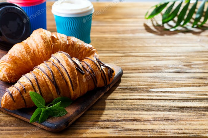 To Go breakfast croissant and coffee on wooden background , copy space