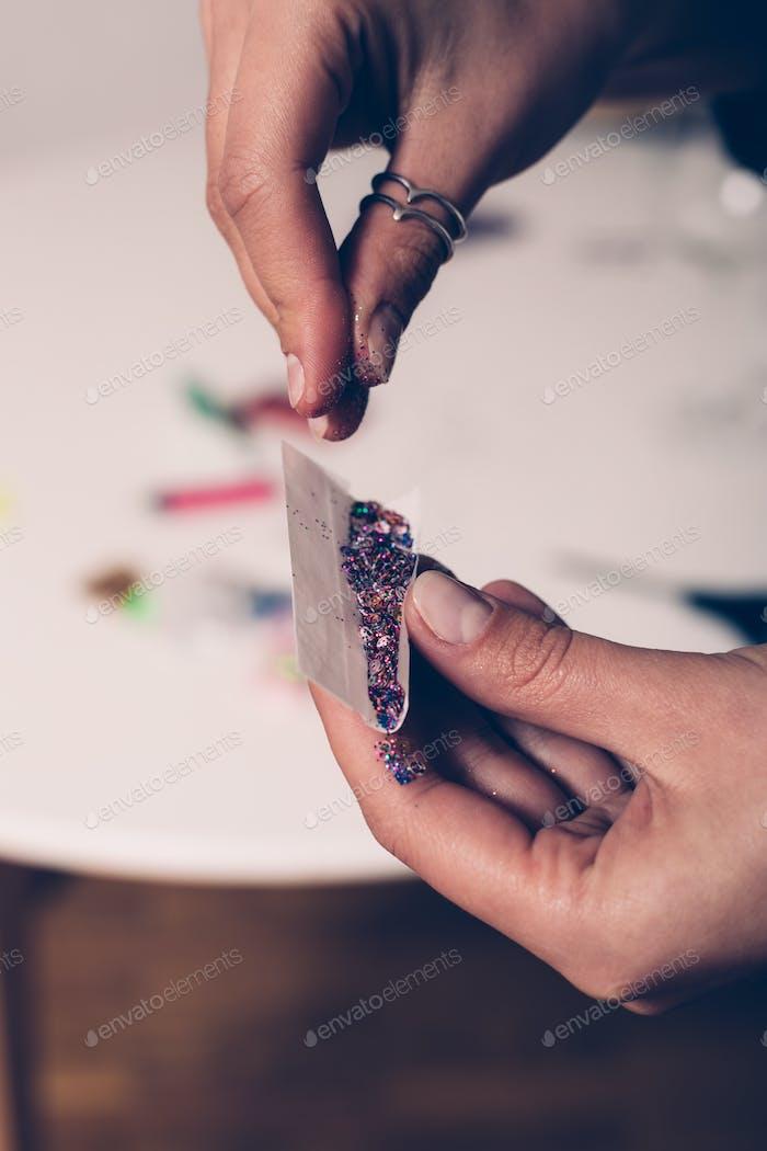 Hände rooling Tabakpapier mit Glitzer innen