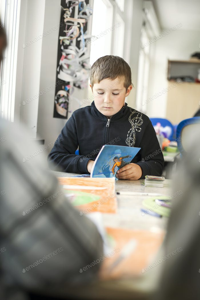 Elementary boy studying at table in classroom