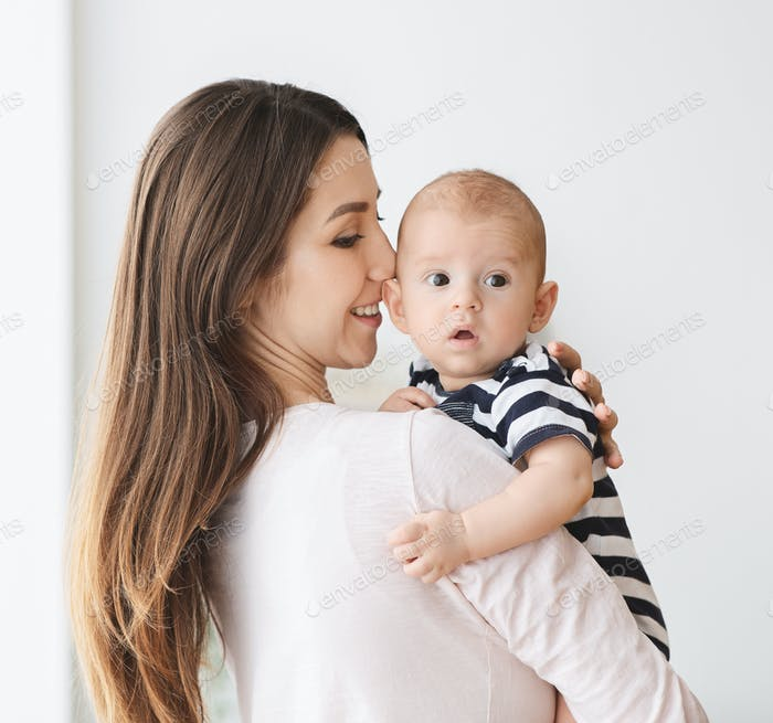 Portrait of beautiful mother with cute infant baby in arms