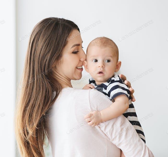 Porträt der schönen Mutter mit niedlichen Baby in den Armen