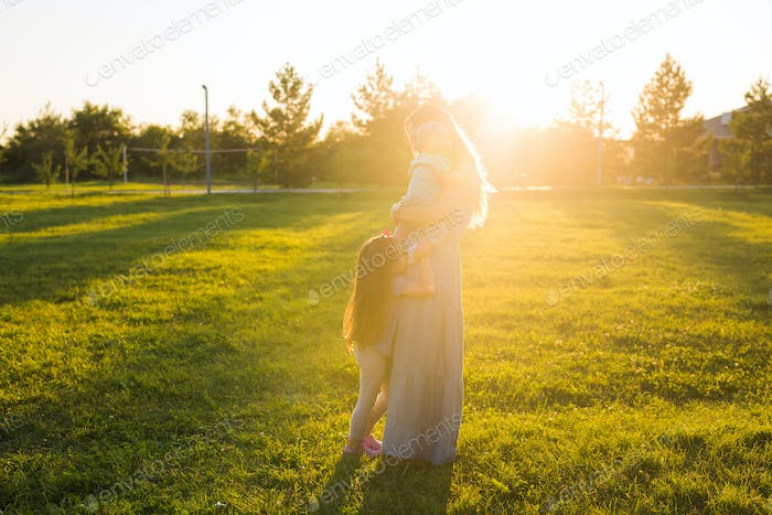 Mother with two little children hugging outdoors. Happy family concept