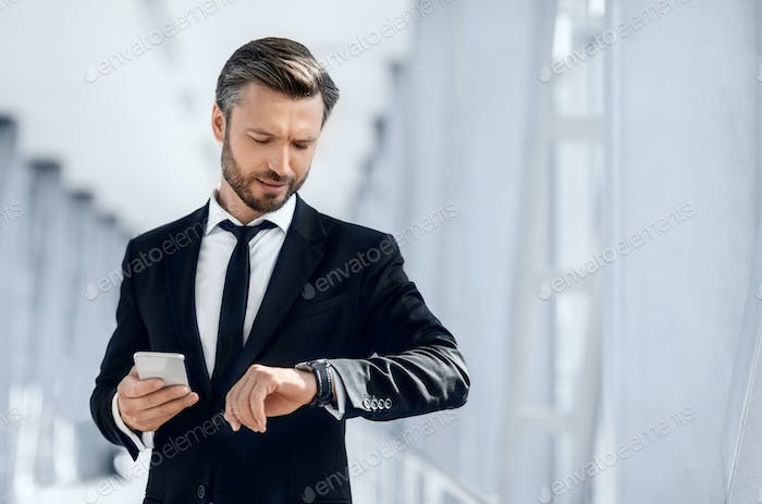 Handsome bearded businessman checking time while waiting for flight