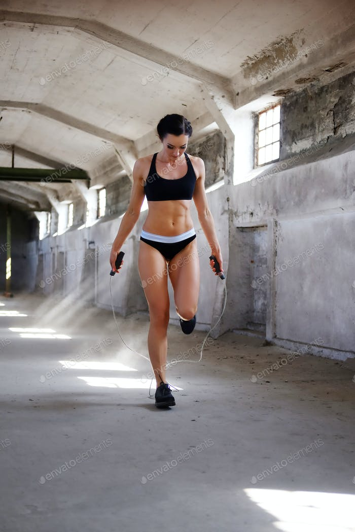 Fitness female jumping with rope.