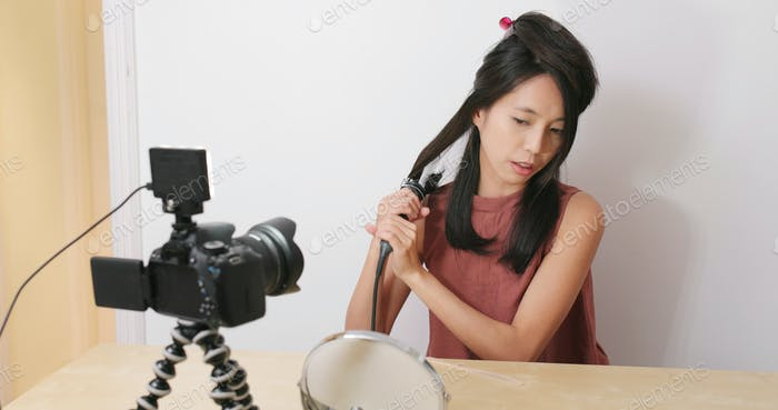 Woman showing hair curler in front of the digital camera and showing how to use for making vlog