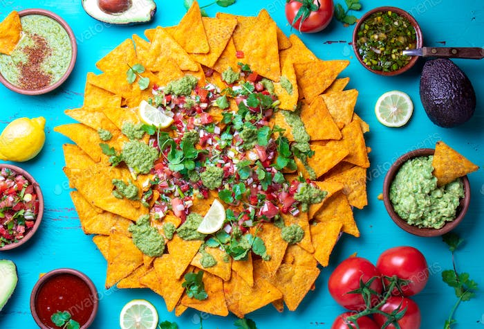 Nachos. Mexican food concept. Yellow corn totopos chips with different sauces