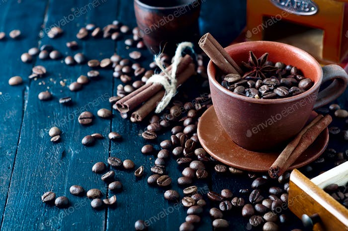 coffee beans in cup with cinnamon sticks and star anise