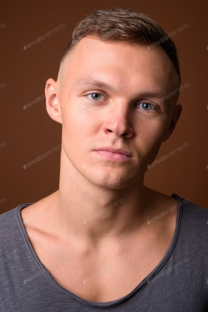 Young man wearing gray shirt against brown background