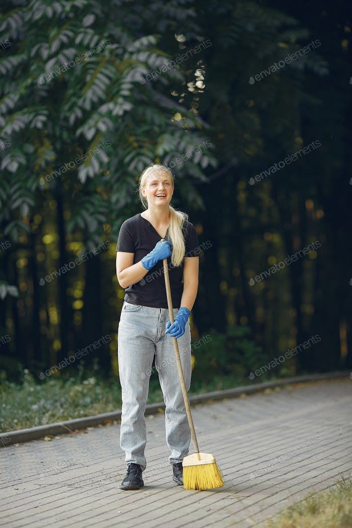 Woman collects leaves and cleans the park