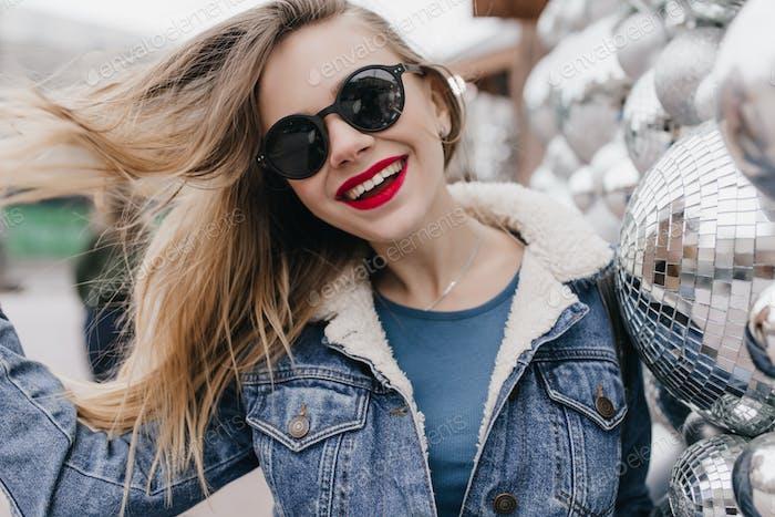 Chica extática con cabello castaño claro disfrutando de la mañana de primavera. Mujer joven elegante en una chaqueta de mezclilla