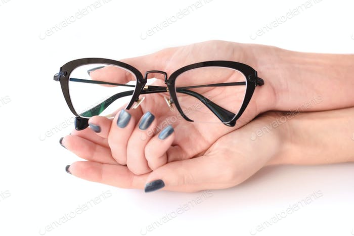 Female hands holding eye glasses on white background