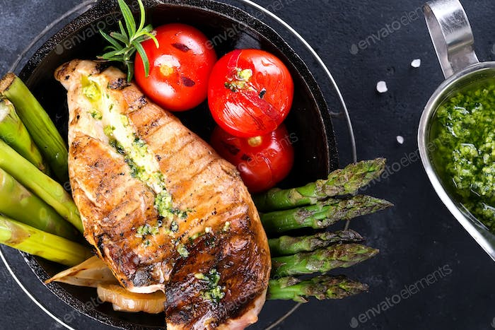 Grilled chicken breast on a cast iron skillet with grill vegetables and green sauce on a stone