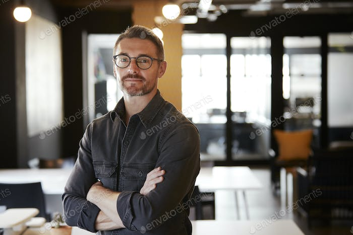 Middle aged white male creative wearing glasses standing in an office looking to camera, waist up