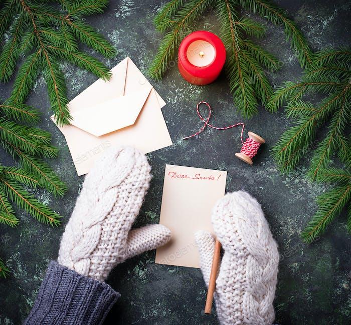 Mädchen in Fäustlingen schreiben Brief für Santa