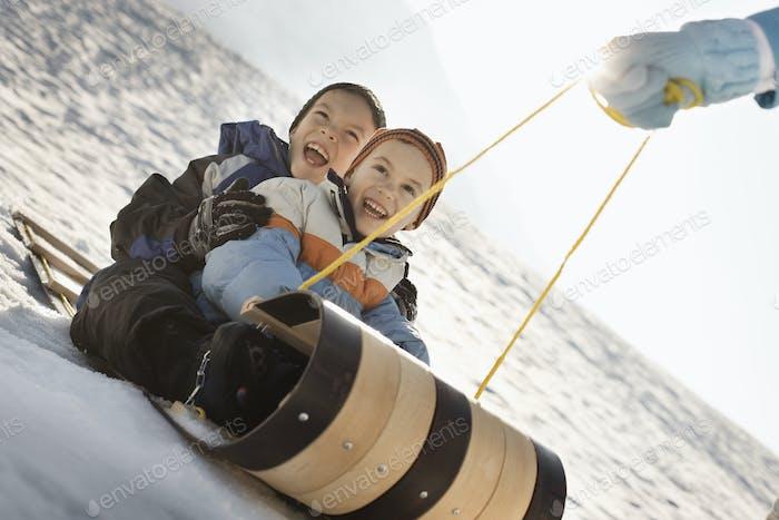Eine Person, die zwei Kinder auf einem Schlitten mitzieht.
