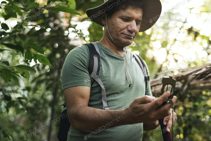Man holding compass in the forest